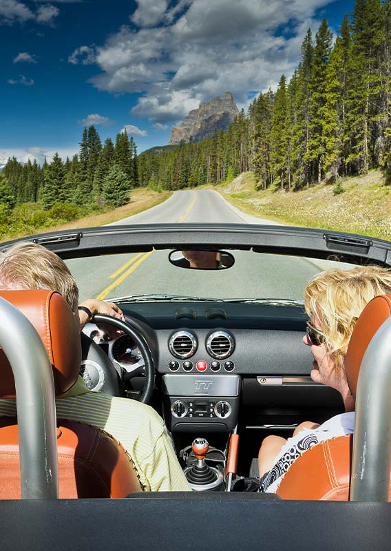 Two people driving a convertible car down an open road between forests.