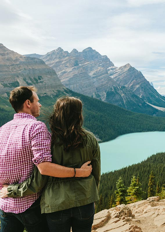 Two people stand overlooking a turquoise lake between forested mountains.
