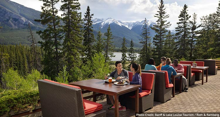 People sit at tables on a patio overlooking a forested valley between tree-covered mountains.