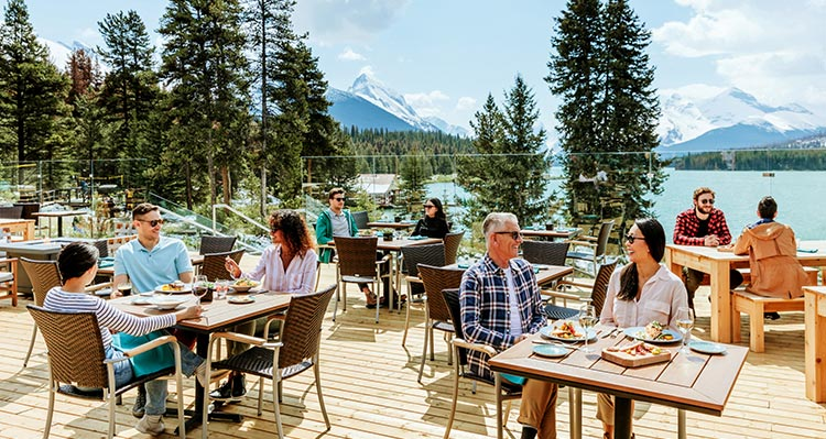 Groups of people sit at tables on a patio overlooking a large blue lake.