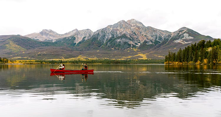 A canoe glides along a clear lake below tall mountains.