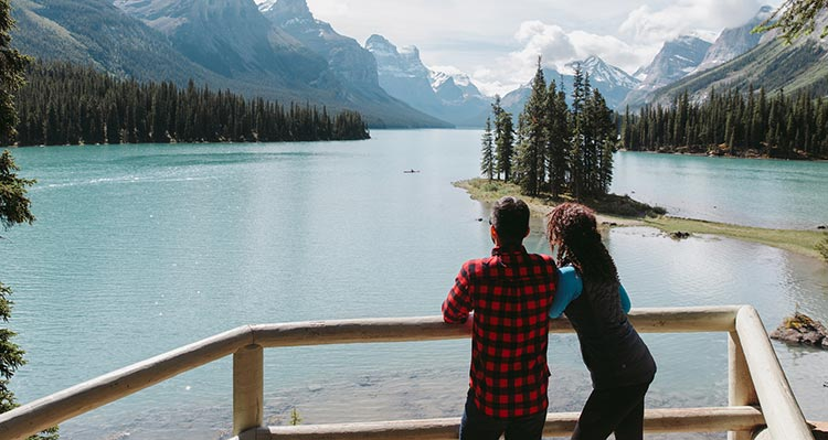 Two people stand at a viewpoint, looking out at a large mountain-sided lake.