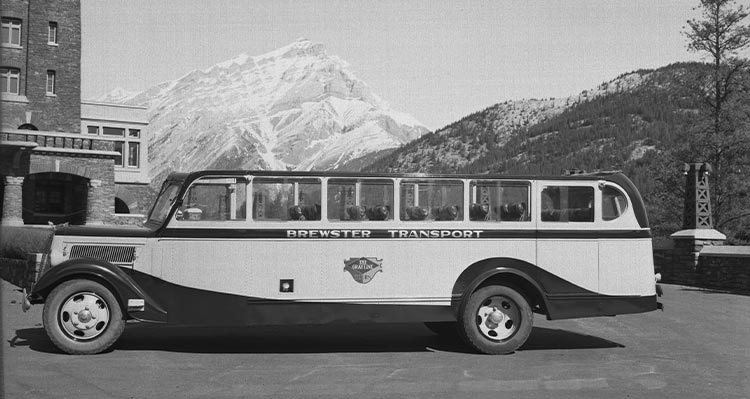 A historic photo of a tour bus parked in front of a stone building and snow-covered mountains.