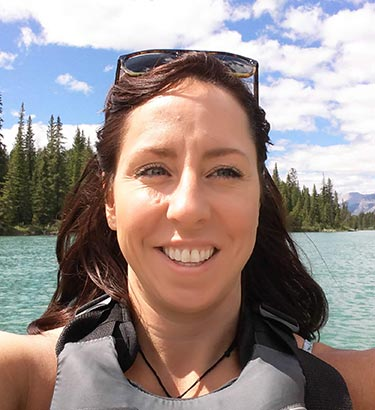 A selfie of a woman on a boat with a conifer forest behind her.