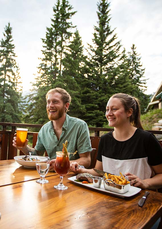 A group of people sit for dinner on a patio overlooking a conifer forest.
