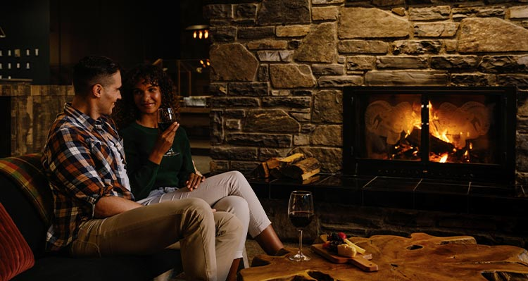 Two people sit at a fireplace.