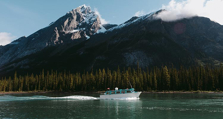 A boat cruises on a blue lake below snowy mountains.