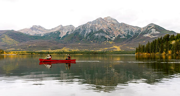 Two people in a canoe on a calm lake below a mountainside.