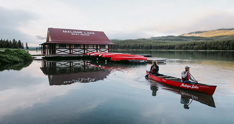Two people canoe away from a lakeside boathouse.
