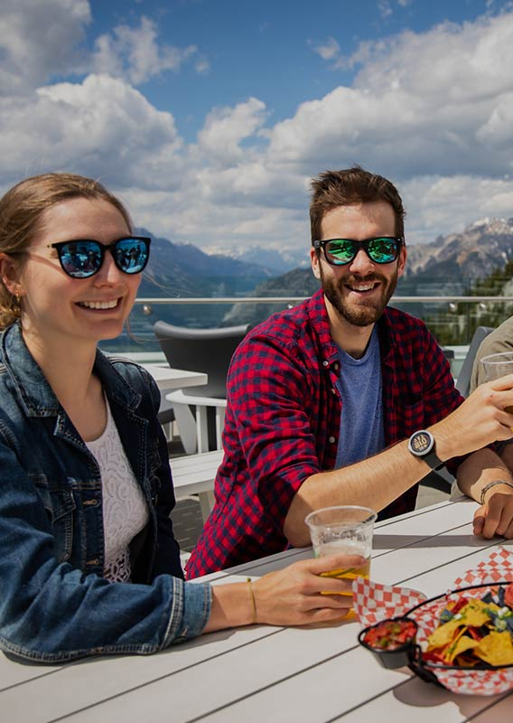Friends sit together on rooftop patio in mountains