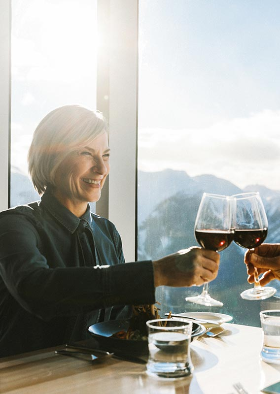A couple raise wine glasses in a cheers at a windowside table overlooking mountains.