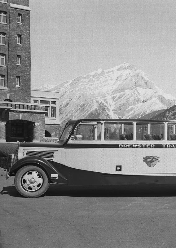 A historic photo of a tour bus parked in front of a large stone building with mountains in the back.