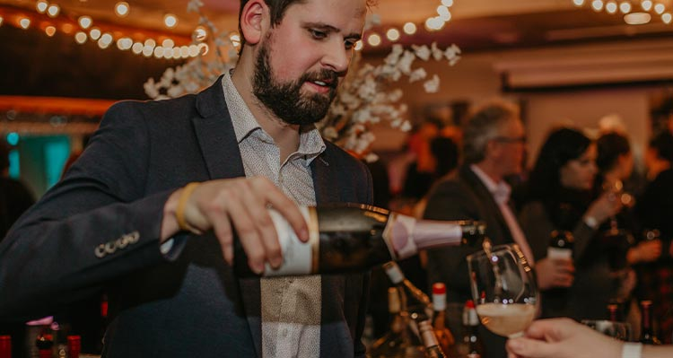 A bearded man pours a glass of champagne.