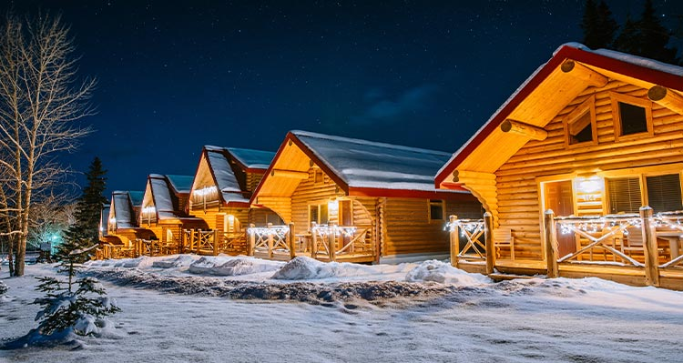 A row of wooden cabins covered in snow and lit up at night..