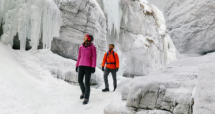 Two people walk through a frozen canyon.