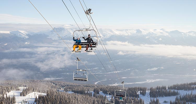 Two people with snowboards sit on a chairlift.