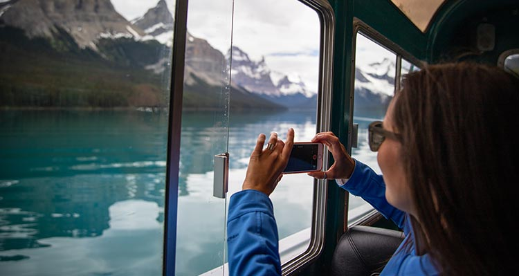 A person holds a camera up to a boat window to take a photo of a mountain landscape.
