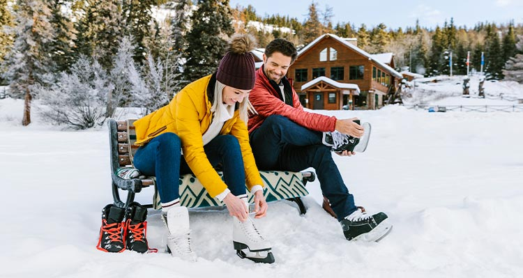 Two people sit on a bench, putting on ice skates.