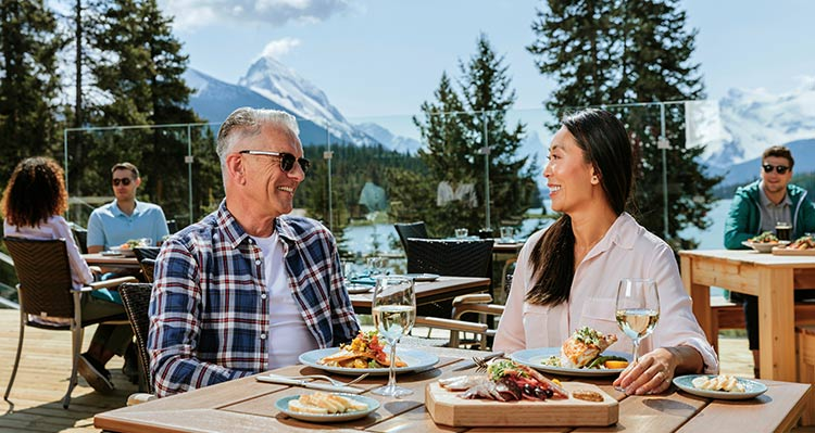 Two people sit at a dinner table on a patio by a lake.