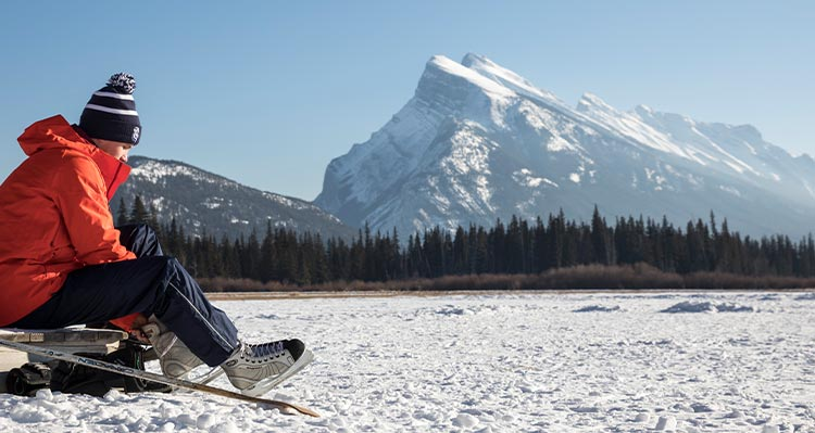 A person ties up their ice skates at the edge of a frozen lake.