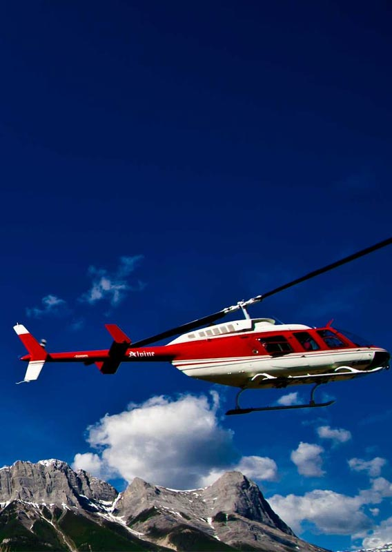 A red and white helicopter takes off under a blue sky and mountains.