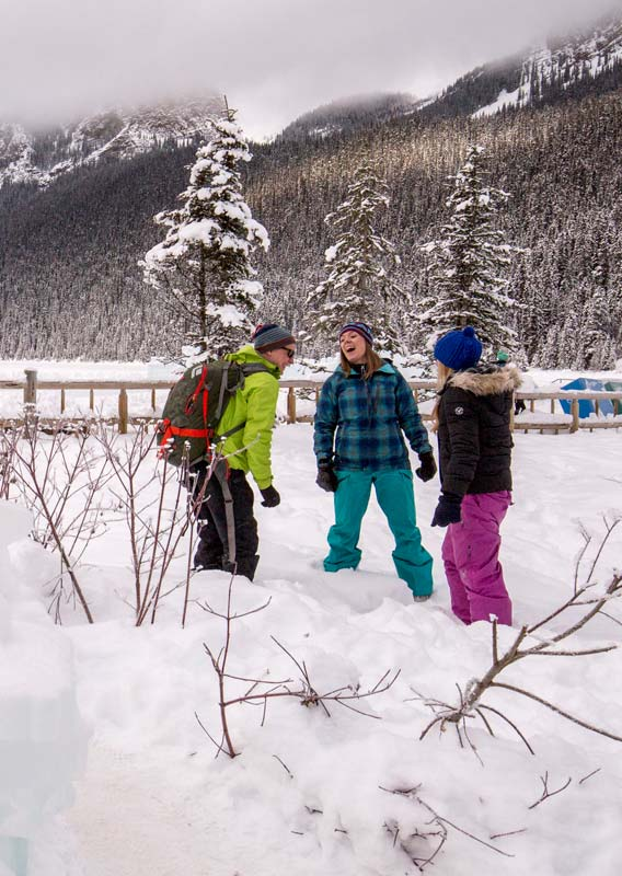 Three people smile and laugh in a winter wonderland scene next to an ice-carved Lake Louise sign.