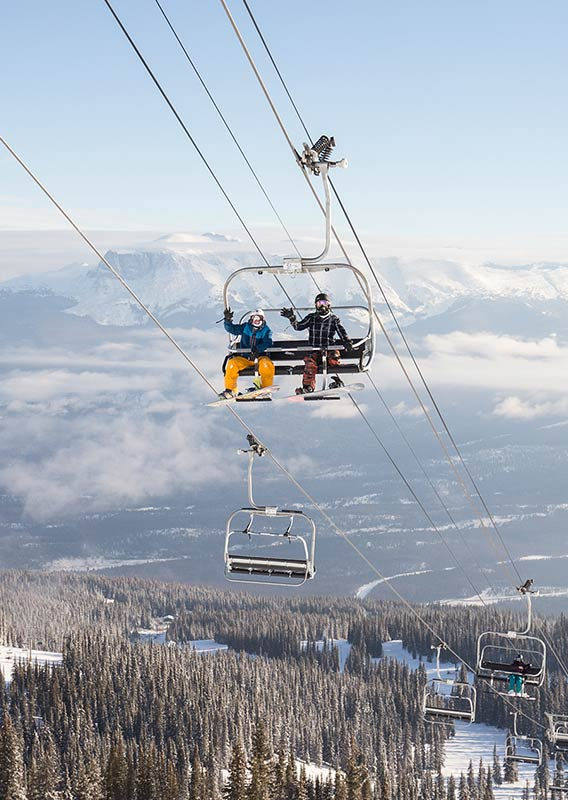 People wave from a chairlift above a forested, snow-covered mountainside.