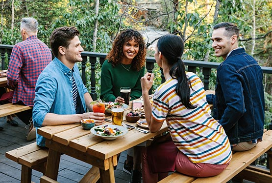 A group of friends sit around a picnic table on a patio next to a forest.