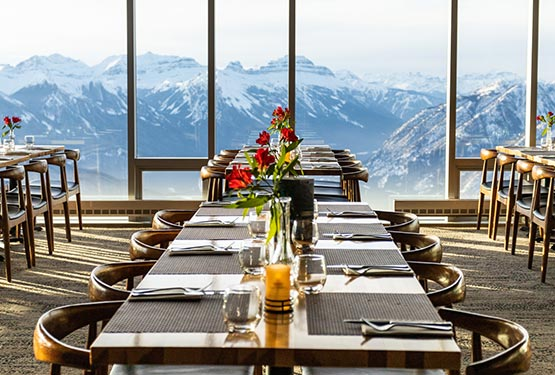 A dining table set with flowers, and a tall window overlooking snow-covered mountains.