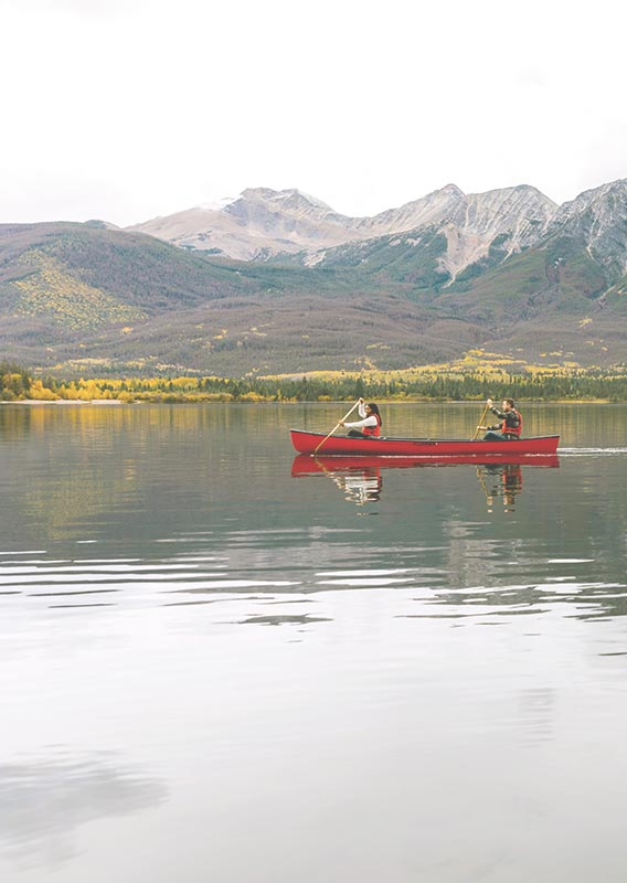 Two canoeists paddle along a clear lake below forested mountainside.