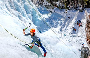 A person ice climbs on a frozen waterfall.