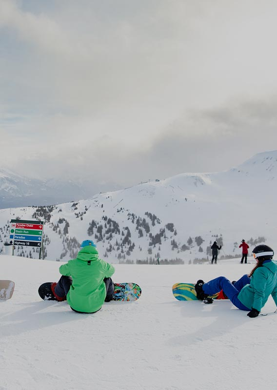 A group of snowboarders relax on a snowy mountaintop