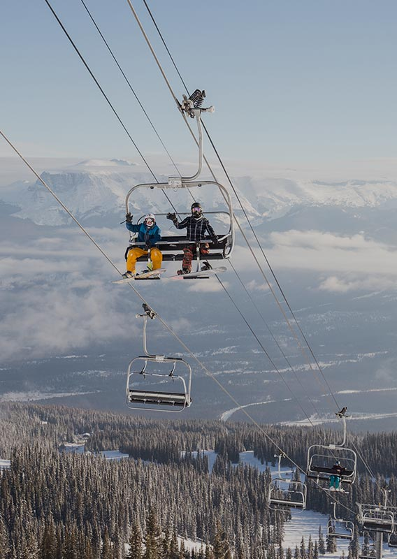 A chairlift with two snowboarders goes up a mountainside