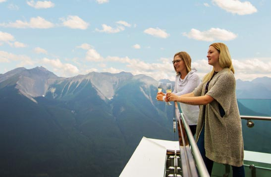 Two women stand at a balcony, overlooking mountains, holding glasses of sparkling wine.
