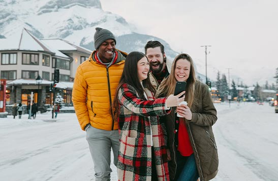 A group of people take a selfie on a snowy street.