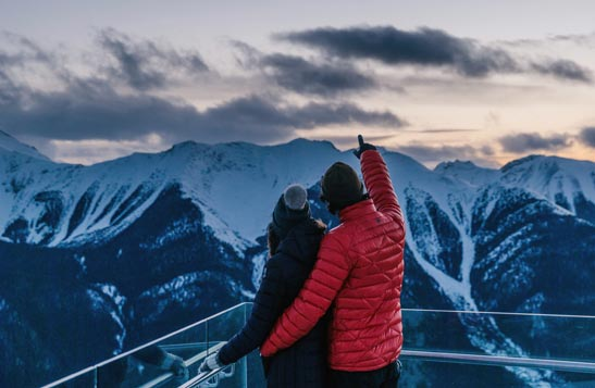 Two people look out towards snowy mountains and the dusky sky.