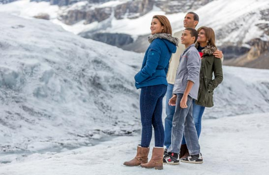 A family stands on a glacier.