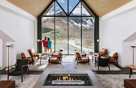 A modern-rustic lounge overlooking an expansive view of a glacier and mountains.