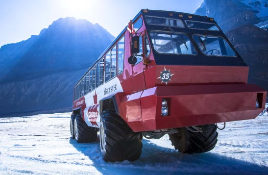 A big red bus with heavy-duty tires on an icefield surrounded by mountains