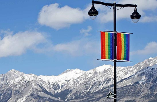 Snow covered mountains behind pride flags hanging from a lamp post.