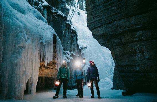 A group of people stand in an icy cavern