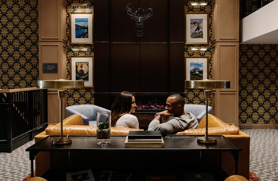 Two people sit in a leather sofa in a luxury hotel lobby