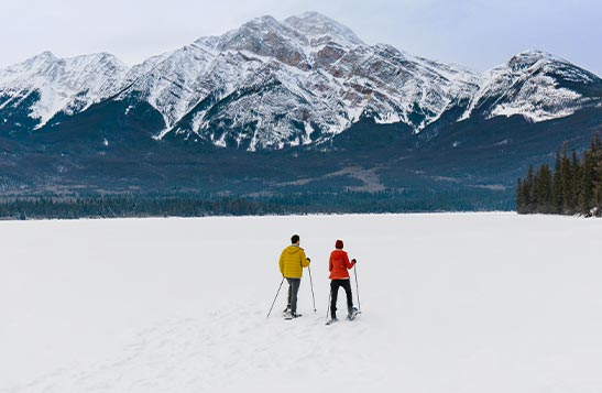 Two people snowshoe across an open snow-covered lake.
