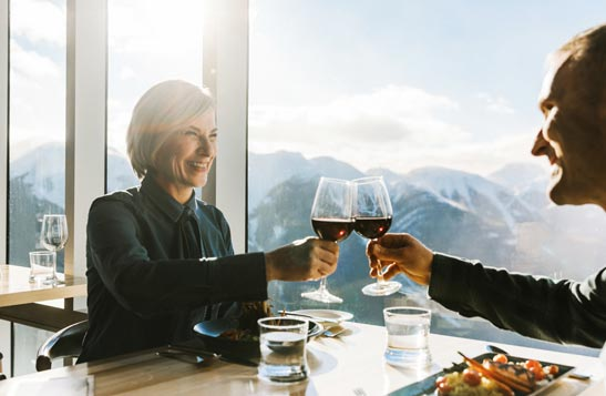 Two people raise glasses in a cheers at a windowside table overlooking snowy mountains.