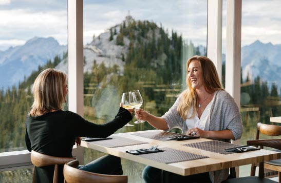 Two women raise wine glasses in cheers, with a wide window view of mountains.