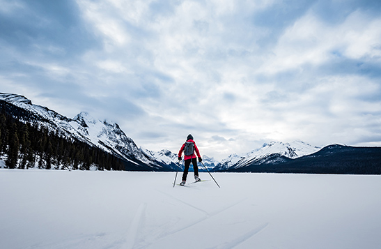 Person in a red jacket cross-country skiing with snowy mountains in the background